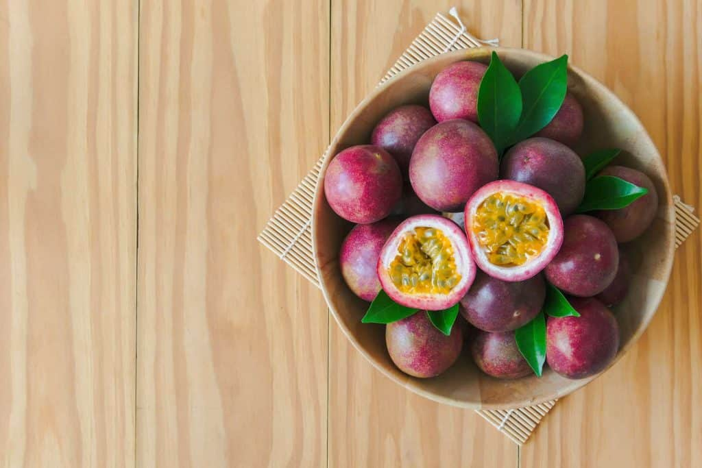 Passion fruit in wood bowl on kitchen table, as a summer decor centerpiece