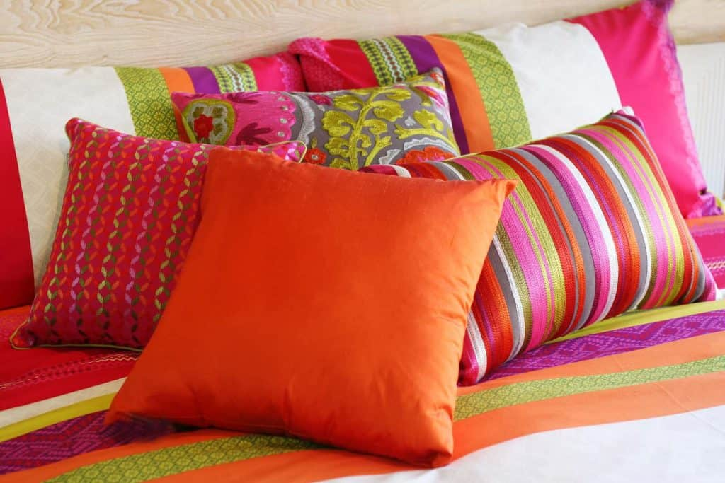 Colorful bedroom pillows as an inexpensive summer decorating idea