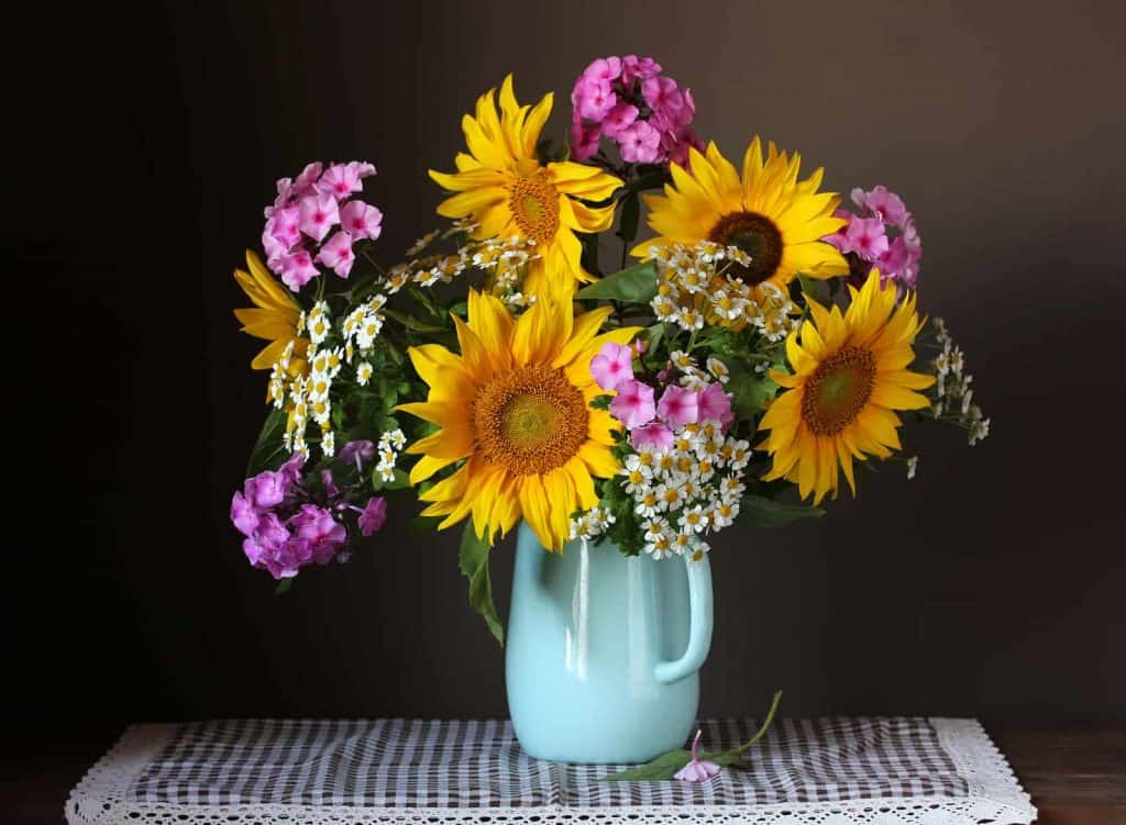 Bouquet of summer flowers in jug on kitchen table
