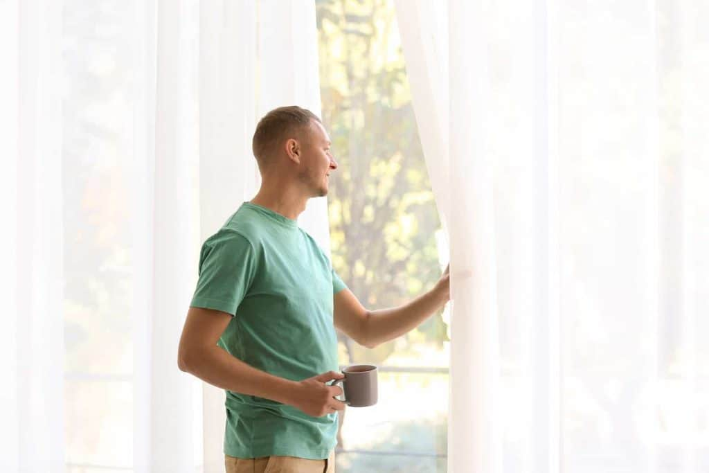 Man opens sheer curtains letting in summer morning light into his home