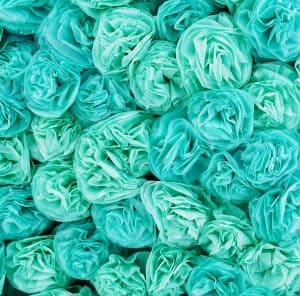 Turquoise tissue paper pom poms stacked on top of each other