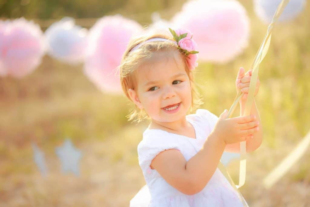 Toddler girl celebrates birthday outside with tissue paper pom poms on a string in the background