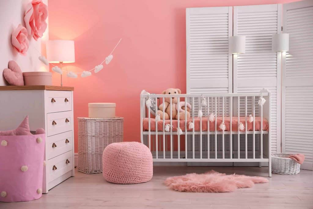 Girl's baby room interior with pink painted walls and dainty decorations such as tissue pompoms