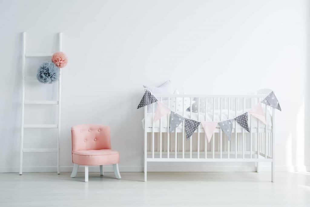 Baby room decor with crib, chair, and decorative ladder with tissue paper poms