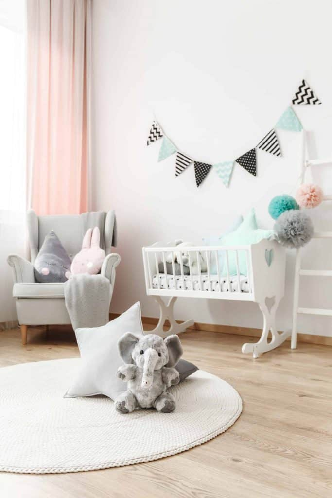 Baby room interior with crib, plush animals, and decorative tissue paper poms