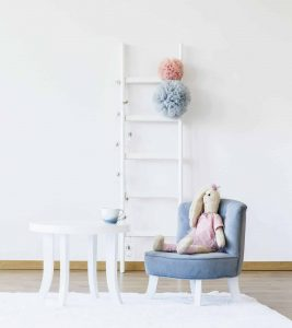 Minimalist child's room decor including play table, chair, stuffed animal, and decorative white ladder with colored tissue paper poms