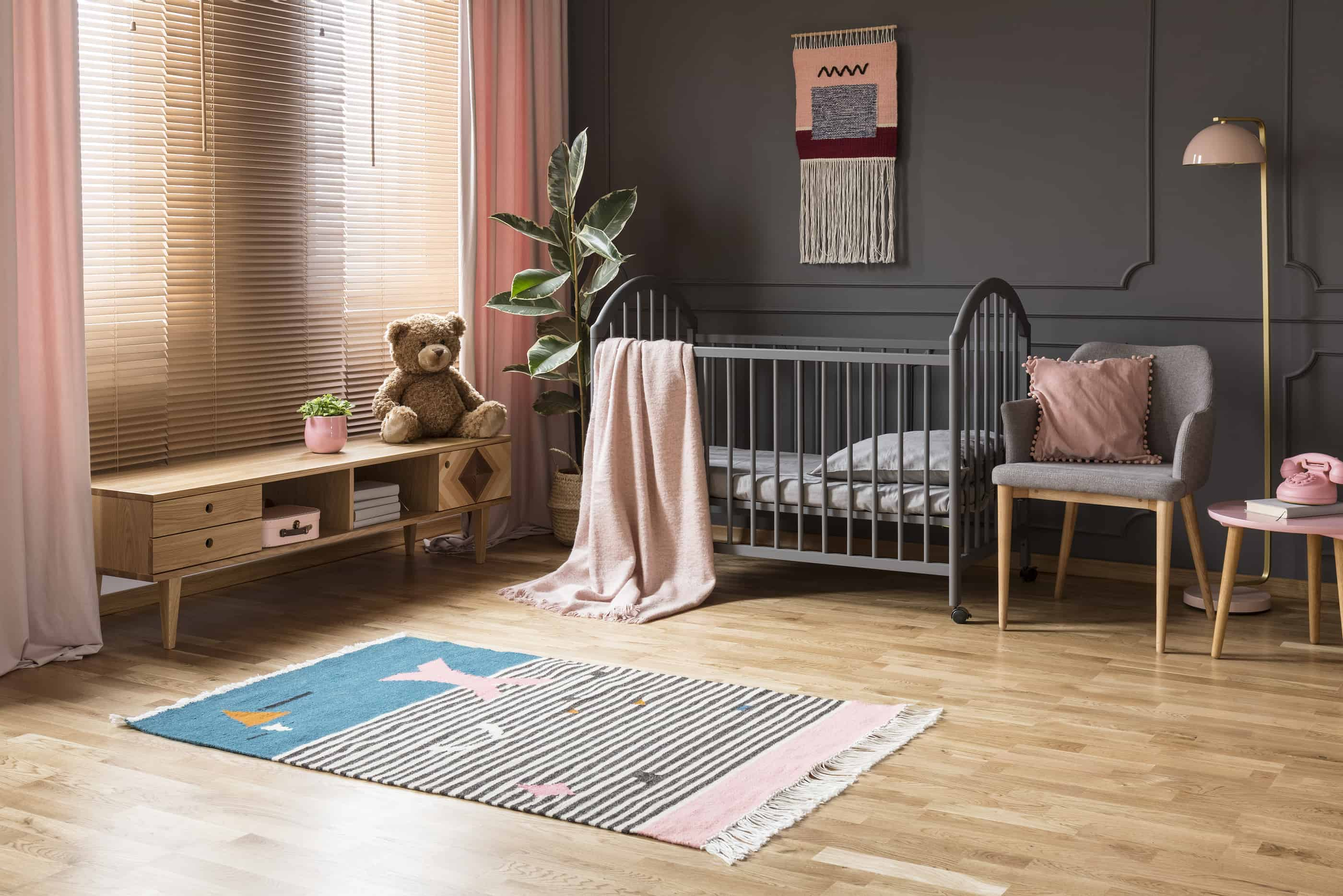 Remodeled baby room and nursery with natural light filtering into through the window with dusty rose curtains on the gray painted walls