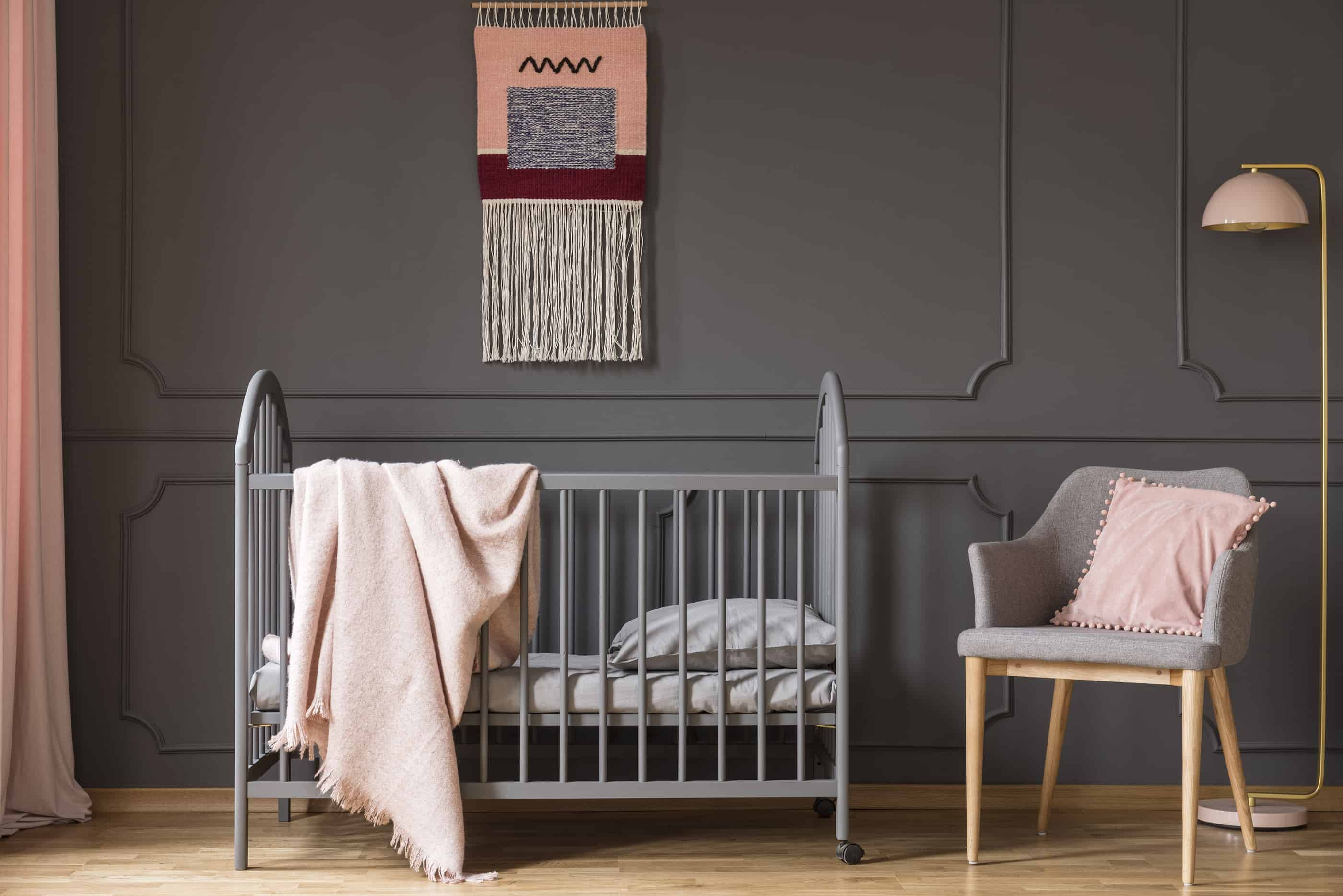 Baby girl's nursery with gray wall, crib, and sitting chair, with a soft, pink blanket draped over the crib