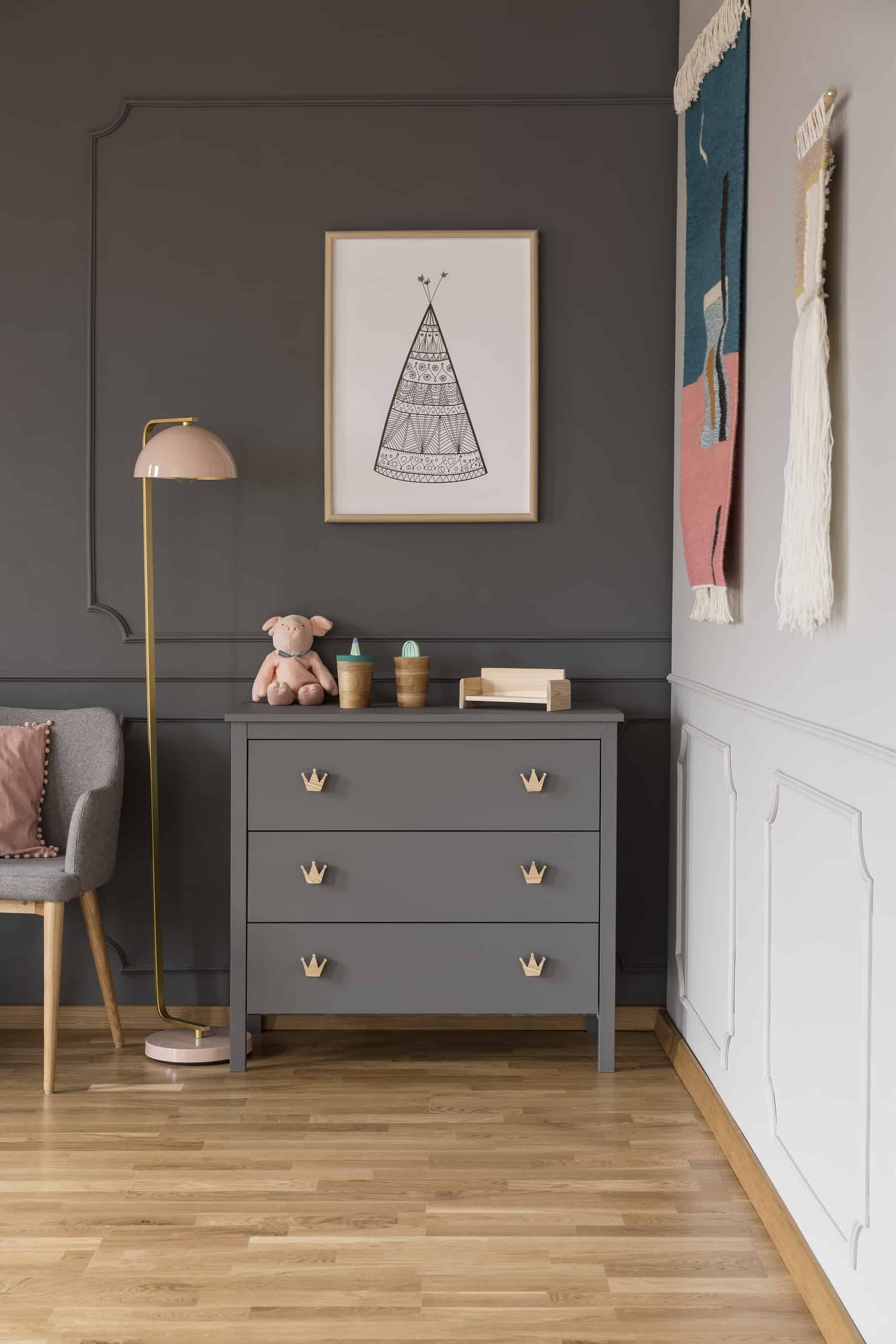 Baby girl's nursery details including a lamp and dresser alongside gray and white painted walls