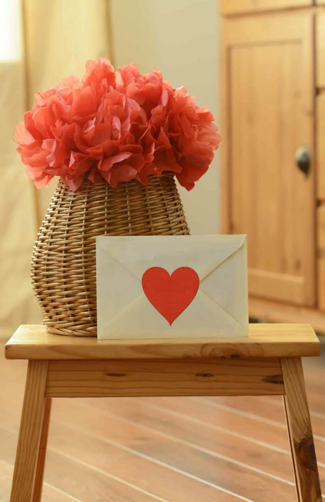 Valentine's Day decoration with red tissue paper pom pom in vase next to an envelope with a red heart