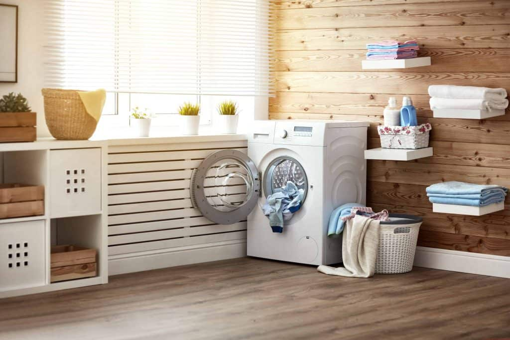 Laundry room decor with white shelves and wood walls and floors