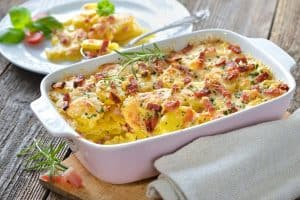 Cheesy, potato gratin dish served in ceramic pan with a plate of food in the background