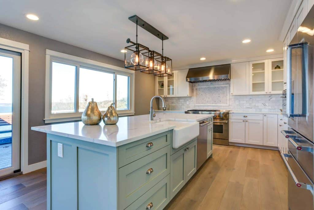 Open kitchen with large marble island with blue-green painted cabinets and a farmhouse sink