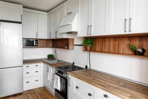 Kitchen renovated with new, white cabinets, steel appliances, and wooden countertop
