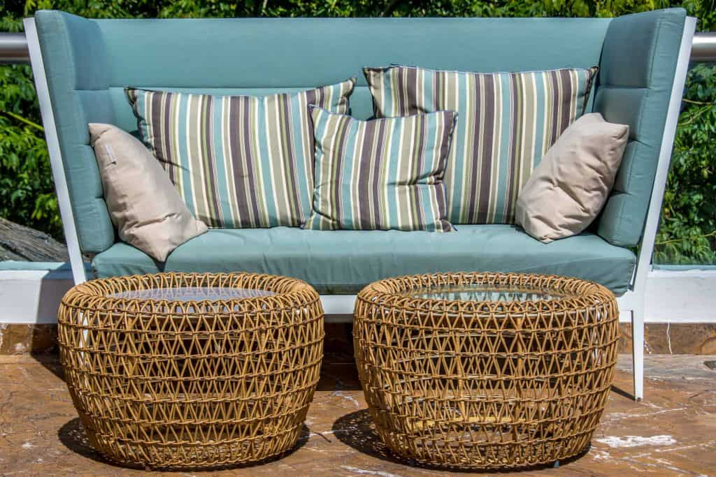 Patio furniture including large, teal couch with two wicker ottomans topped with custom glass