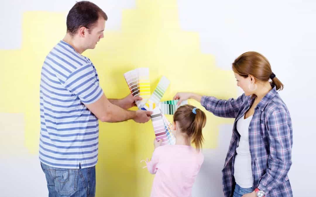 Young family compares interior paint colors on several paint swatches