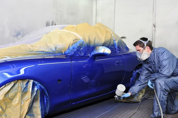Auto paint technician spraying a new coat of paint onto a car