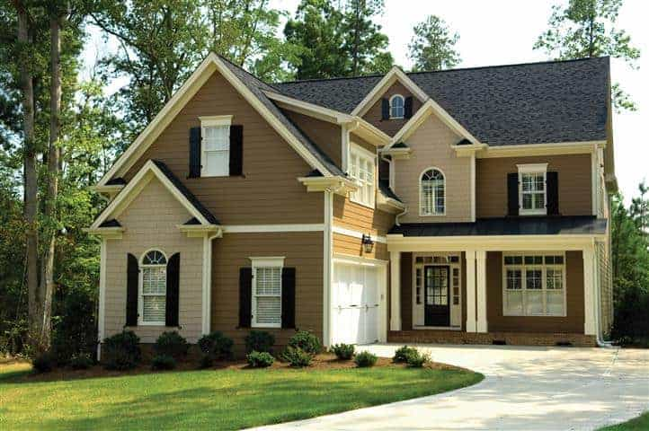 Two-story home painted with brown and tan exterior paint and cream trim