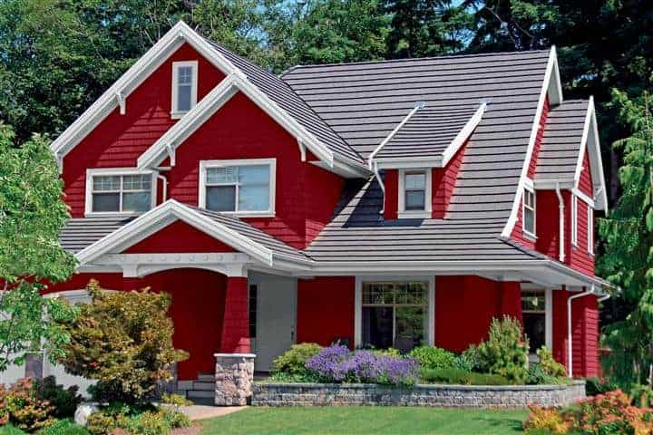 Home with red exterior house paint on wood siding and white wood paint along trim