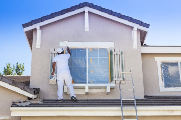 House painter applying exterior paint to a home's window trim
