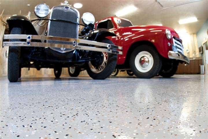Close-up of garage epoxy floor coating and two vintage cars parked inside the garage