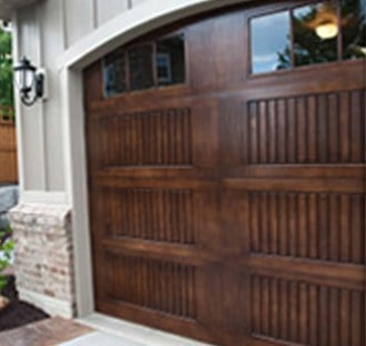 Custom residential wood garage doors with unique detailing and small windows