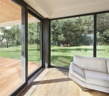 Floor-to-ceiling vinyl windows letting in natural light and opening to wood deck and forested backyard