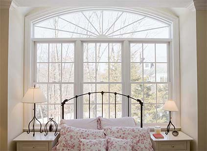 Beautiful wooden windows surround child's bed frame and night stands