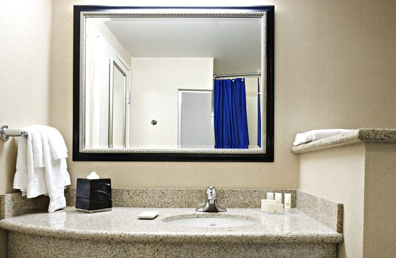 Hotel bathroom vanity area with large custom mirror with a black and silver frame