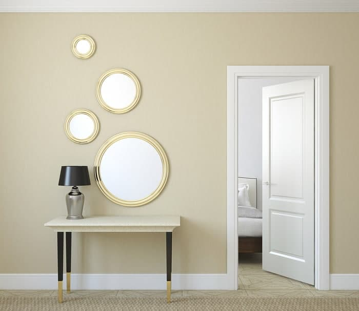 Large and small round home mirrors decorate interior hallway
