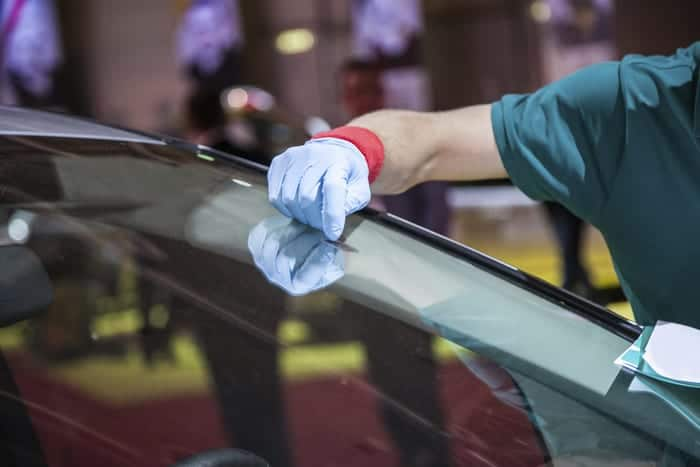 Auto glass specialists repairs rock chips in a vehicle's windshield