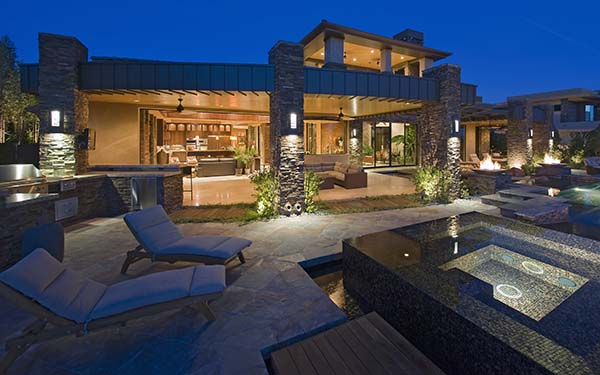 Luxury home at night with composite windows and glass doors opening up to poolside chairs and hot tub