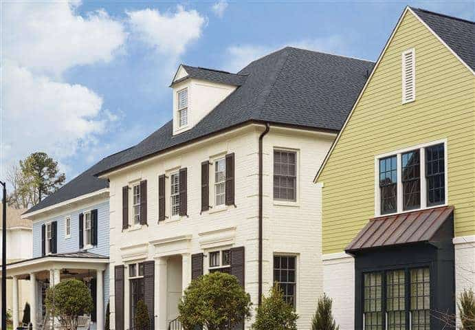 Light blue, cream, and yellow exterior paint colors recently painted onto three adjacent homes