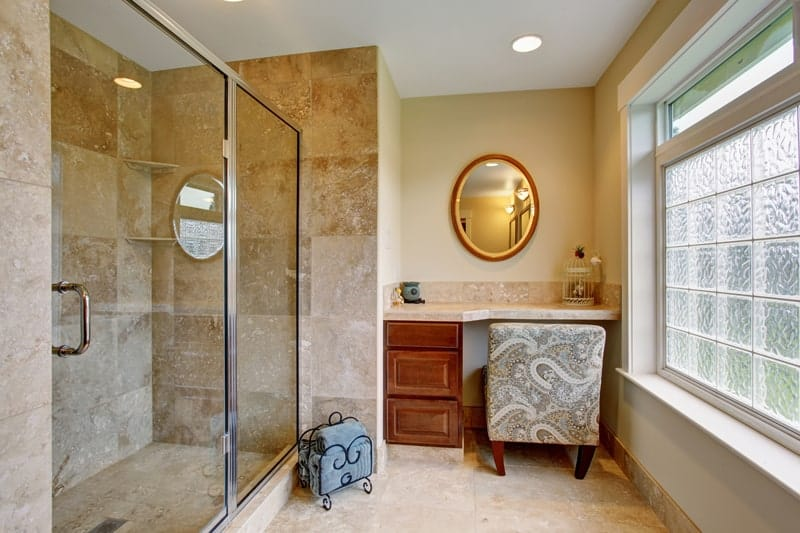 Luxury master bathroom with custom vanity mirror, sliding glass shower doors, and decorative glass windows