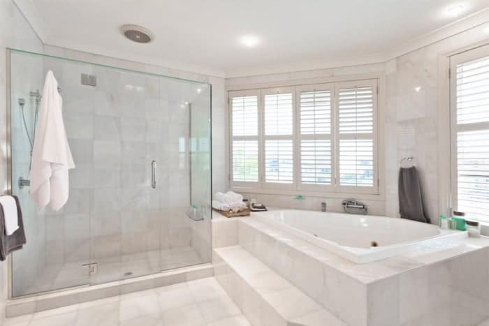 New glass shower doors and jacuzzi bathtub in luxury master bathroom