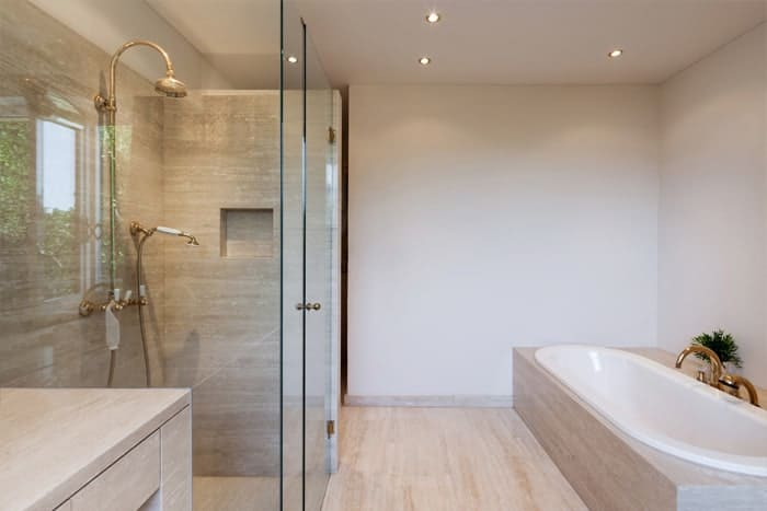 Elegant glass shower doors and bathtub with gold faucets and handles