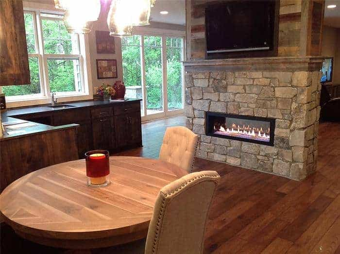 Open kitchen with stone fireplace, wood floors, and fiberglass composite windows in the background