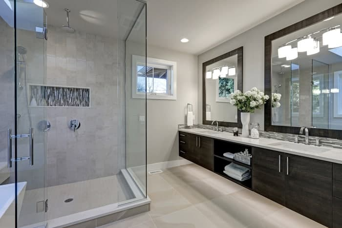 Double sink with custom vanity mirror and frameless glass shower doors in luxury bathroom