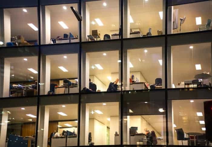 Commercial windows make up the exterior of an office building, looking in floors of desks and office space