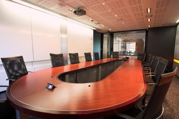 Commercial conference room with oval table and large commercial window in the back