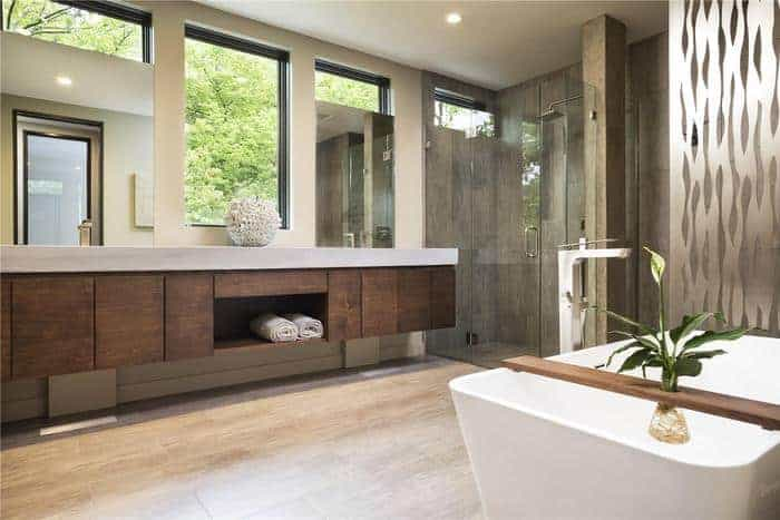 Luxury bathroom with several wood features and frameless shower glass