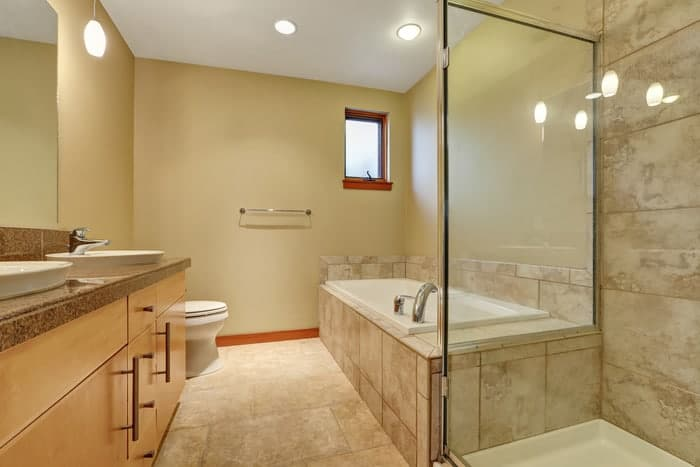 Renovated bathroom with custom glass mirror and shower glass doors