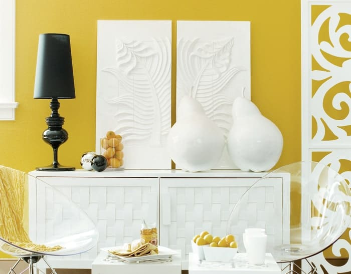 Golden yellow interior paint on the wall behind white living room furniture