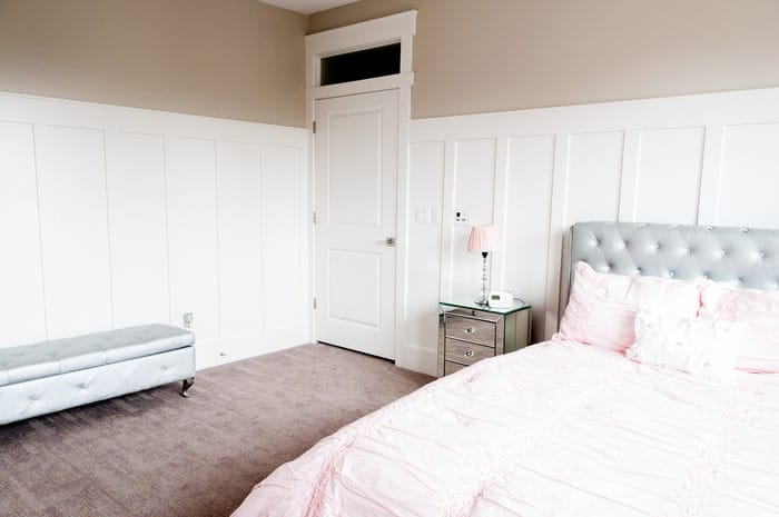 Bedroom with tall, white wainscoting and light tan interior paint above