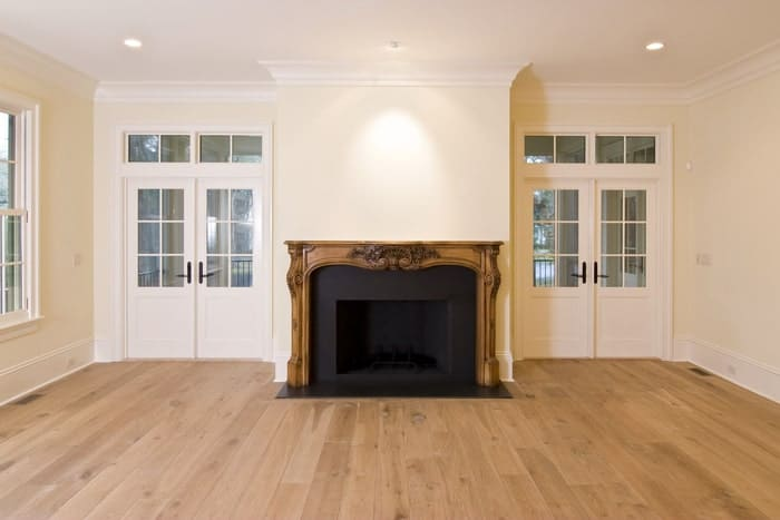 Ornate fireplace, wood floors, and white interior doors with windows