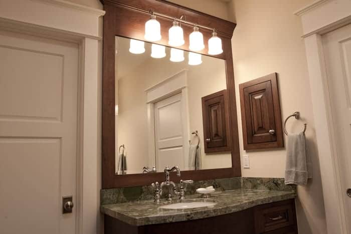 Custom glass mirror fits perfectly in wood frame above bathroom sink