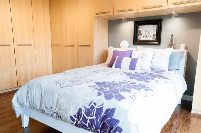 Bedroom wood closets surround bed and look like new with fresh wood stain and finish