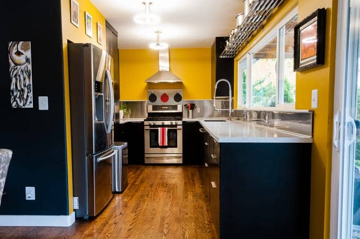 Modern kitchen with stainless steel appliances, yellow painted walls, and large windows above kitchen sink