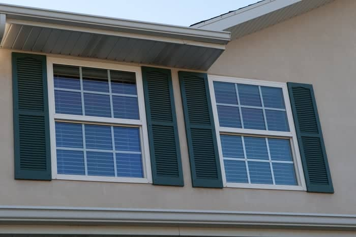 Blue-green window shutters surround new replacement windows on second floor of home