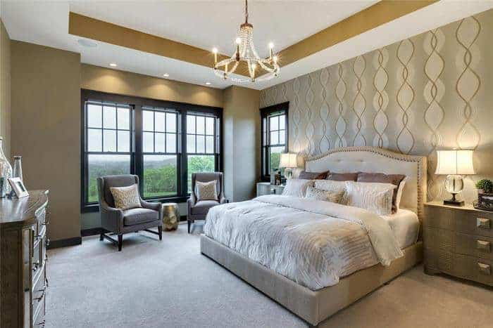 Master bedroom in Utah home with large wood clad windows and luxury furniture